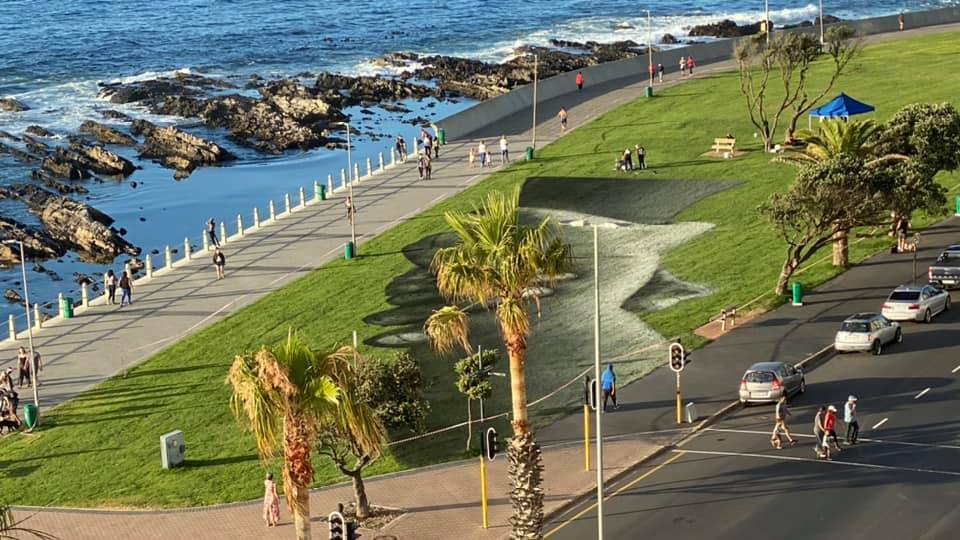 Artist spray paints mural of hope and dialogue on Sea Point promenade